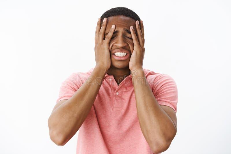 De kerel die aan schuld en verdriet dringende handen lijden aan gezicht die tanden dichtklemmen en ogen het voelen sluiten betreu royalty-vrije stock fotografie