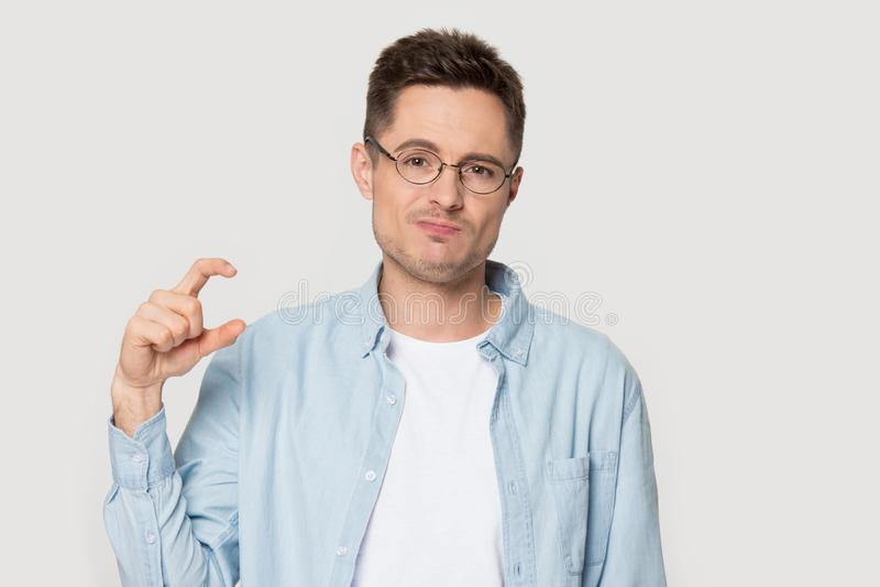 De kerel die van het Headshotportret met vingers klein iets tonen royalty-vrije stock foto