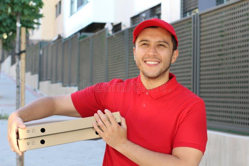 De kerel die van de pizzalevering in openlucht glimlachen stock afbeeldingen