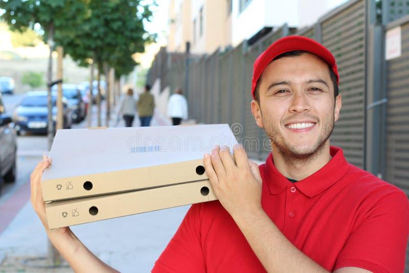 De kerel die van de pizzalevering in openlucht glimlachen royalty-vrije stock afbeeldingen