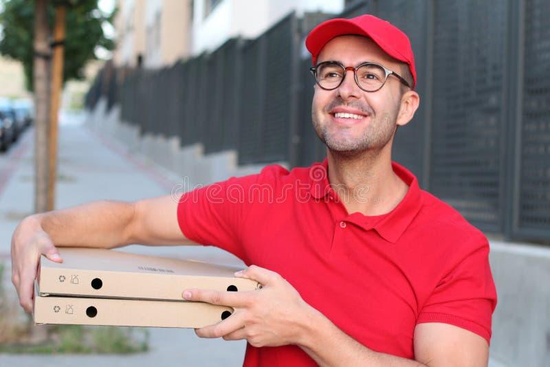 De kerel die van de pizzalevering in openlucht glimlachen stock foto