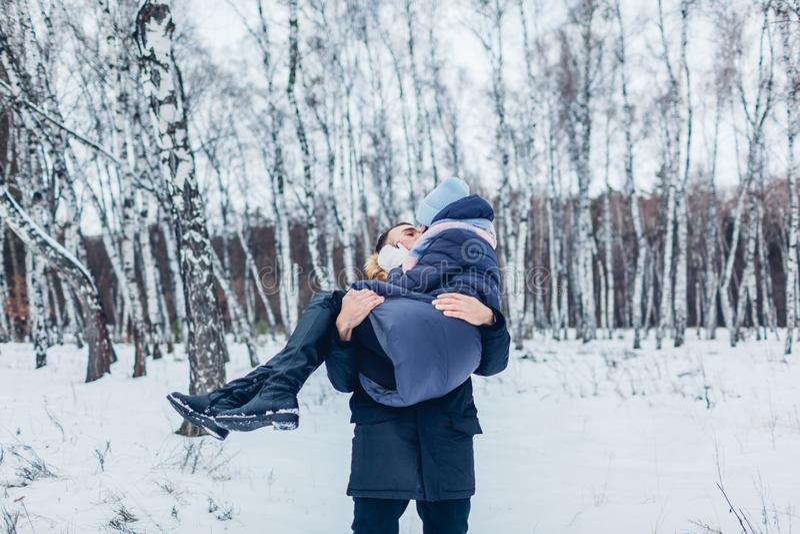 De kerel die zijn meisje vervoeren dient in openlucht de winter bosmensen in die pret hebben stock afbeeldingen