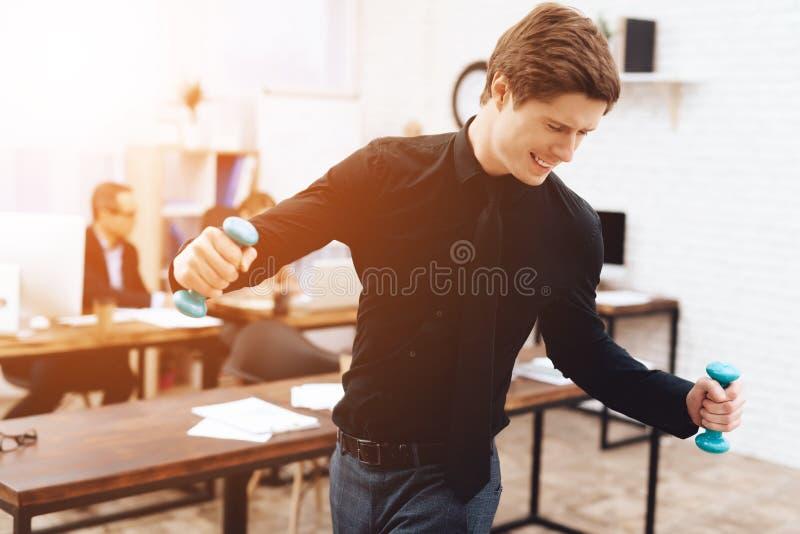 De kerel doet gymnastiek- oefeningen op het werk royalty-vrije stock afbeelding