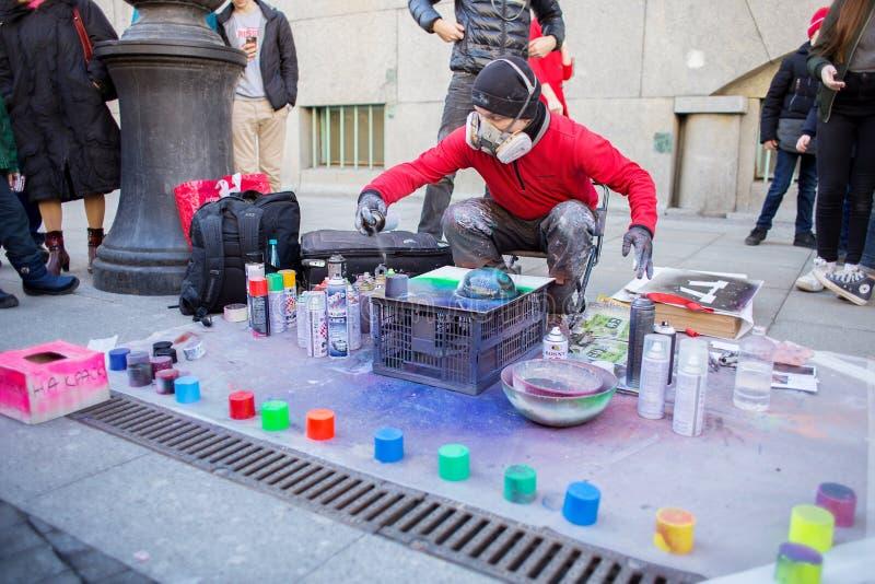 De kerel in een ademhalingsapparaat trekt de verven van een kartnanevel op de straat stock afbeeldingen
