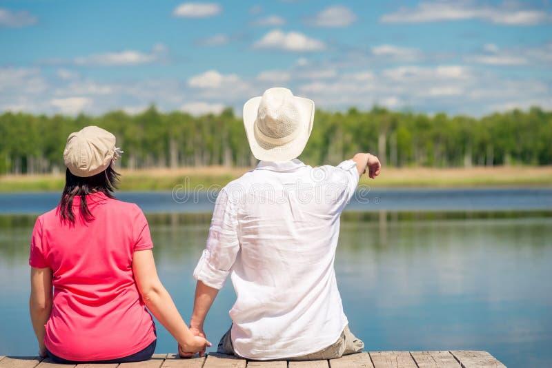 De kerel en het meisje bekijken de meerzitting op de pijler, mening van royalty-vrije stock fotografie