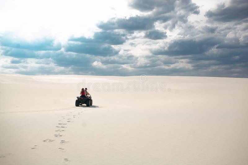 De kerel en het meisje berijden een vierlingfiets in de woestijn, hebbend pret en genietend van, een paar minnaars stock foto's