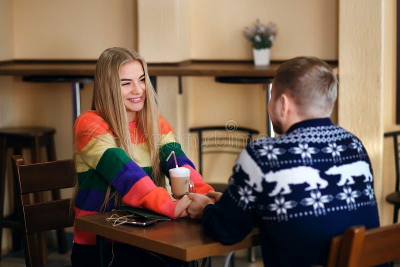 De kerel en het meisje drinken koffie in een koffie, houdt de man de handen van de vrouw, glimlacht het paar in liefde, de kerel stock foto