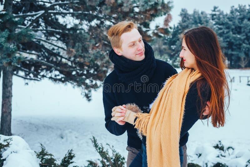 De kerel en het meisje hebben een rust in het de winterhout Echtgenoot en vrouw in de sneeuw Jong paar die in de winterpark lopen stock afbeeldingen