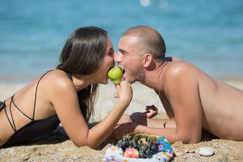 De kerel en het meisje liggen samen het bijten peer de van aangezicht tot aangezicht stock afbeelding