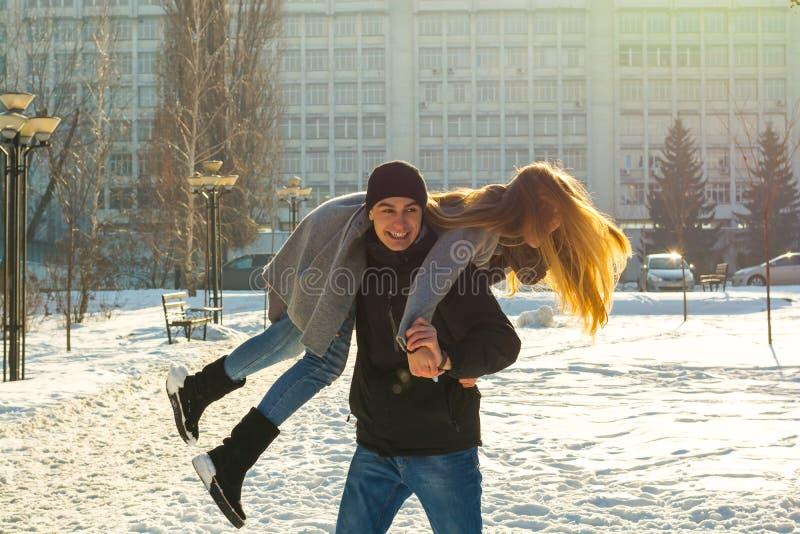 De kerel en het meisje stellen in de winter tevreden, houdt hij haar op zijn schouders en draaien Een houdend van paar speelt bui stock afbeeldingen