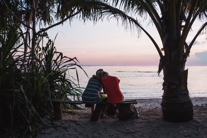 De kerel en het meisjesmodel bekijken het gelukkige leven op een tropisch strand zonsondergang stock foto