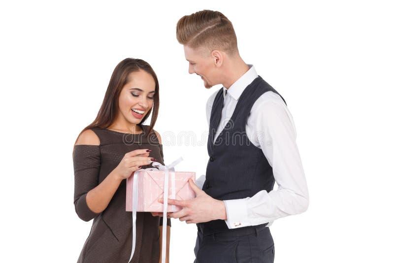 De kerel geeft het meisje een giftdoos Gelukkig paar in liefde Geïsoleerdj op witte achtergrond stock foto