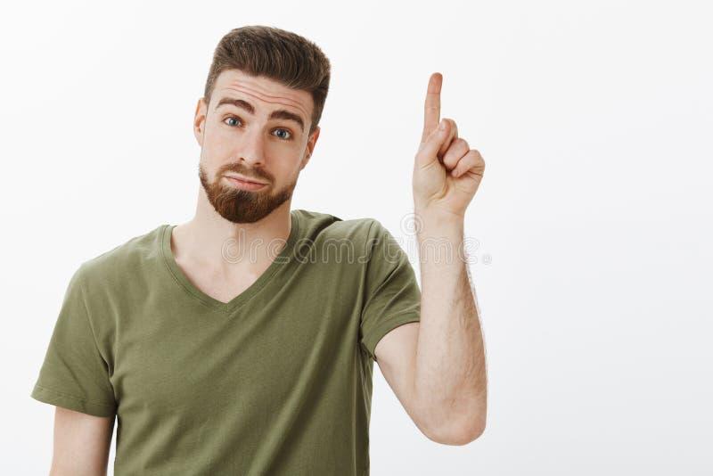 De kerel heeft één suggestie die wijsvinger opheffen idee toevoegen die dwaas en zich leuk met het aarzelende en schuwe uitdrukki stock afbeelding