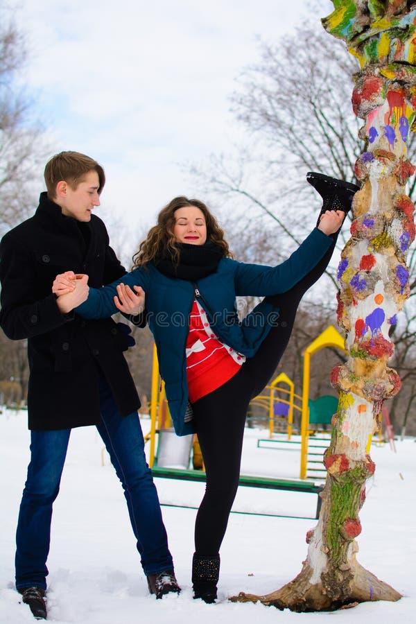De kerel helpt een meisje om het uitrekken dichtbij een boom op de straat te doen zich stock afbeelding