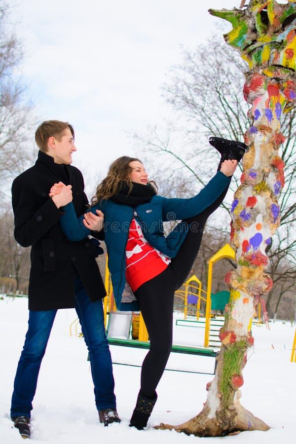 De kerel helpt een meisje om het uitrekken dichtbij een boom op de straat te doen zich royalty-vrije stock afbeelding