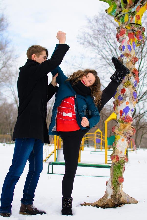 De kerel helpt een meisje om het uitrekken dichtbij een boom op de straat te doen zich stock fotografie