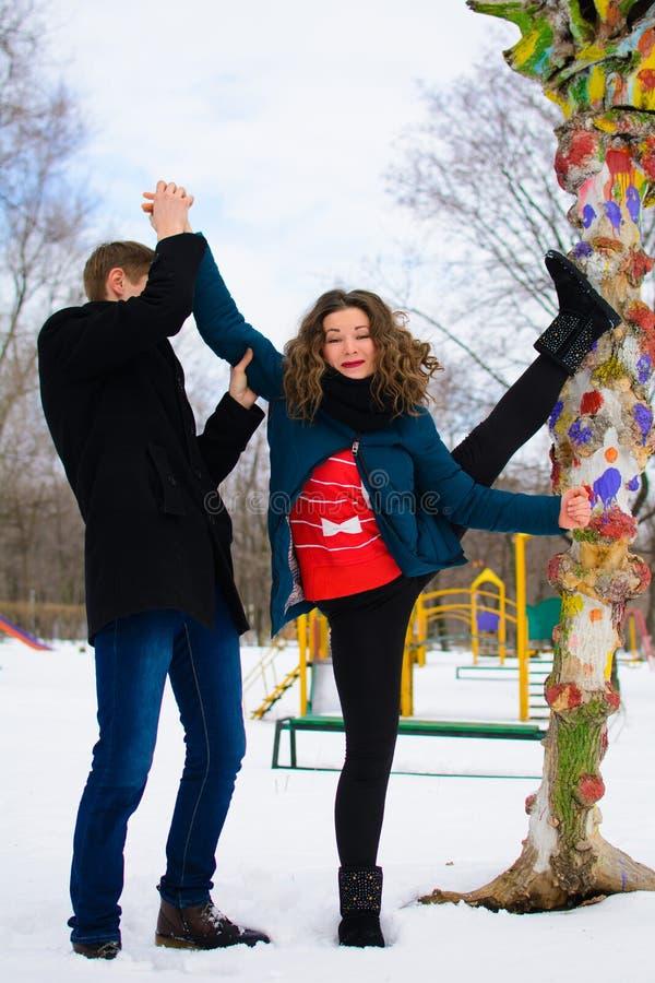 De kerel helpt een meisje om het uitrekken dichtbij een boom op de straat te doen zich royalty-vrije stock afbeeldingen