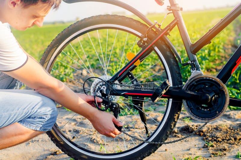 De kerel herstelt de fiets kettingsreparatie fietser unratitude op de weg, reis, close-up royalty-vrije stock fotografie