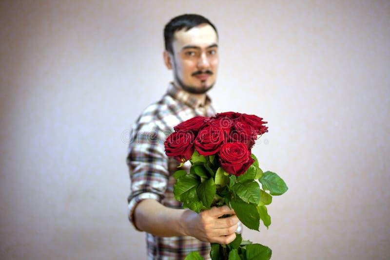 De kerel in het plaidoverhemd houdt een boeket van rode rozen in zijn hand, nadruk op bloemen stock foto's