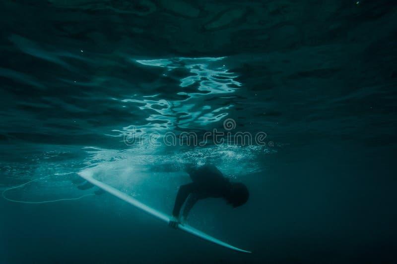 De kerel in het zwarte zwempak die een brandingsraad houden duikt onder de golf royalty-vrije stock afbeeldingen