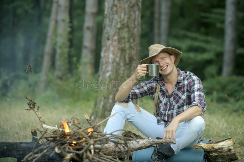 De kerel in hoed zit dichtbij vuur, bomen op achtergrond, defocused royalty-vrije stock afbeelding