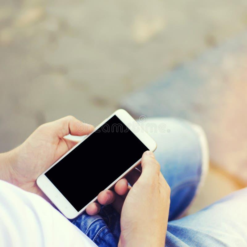 De kerel houdt een mobiele smartphone en bekijkt het scherm telefoonafhankelijkheid, sociale netwerken Het werk aangaande Interne stock afbeelding