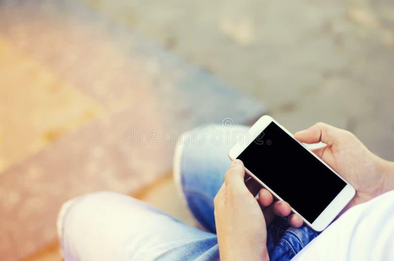 De kerel houdt een mobiele smartphone en bekijkt het scherm telefoonafhankelijkheid, sociale netwerken Het werk aangaande Interne royalty-vrije stock fotografie