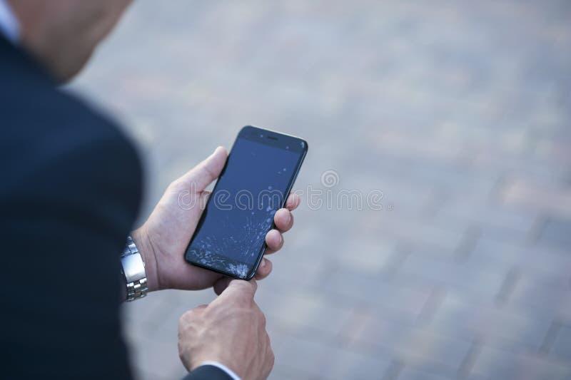 De kerel houdt een smartphone met het gebroken scherm in zijn hand stock foto