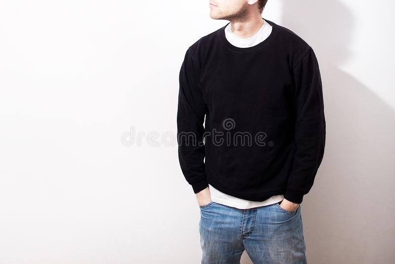 De kerel in Lege zwarte hoodie, sweatshirt die, tribune, glimlachen royalty-vrije stock foto's
