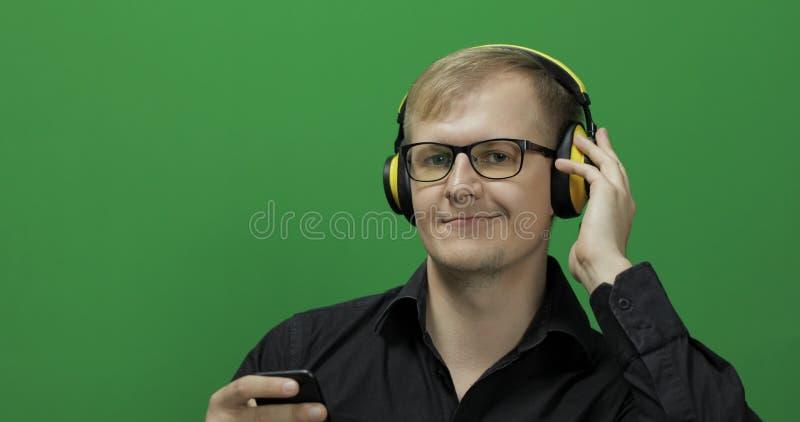 De kerel luistert aan muziek in draadloze gele hoofdtelefoons Het groene scherm stock foto
