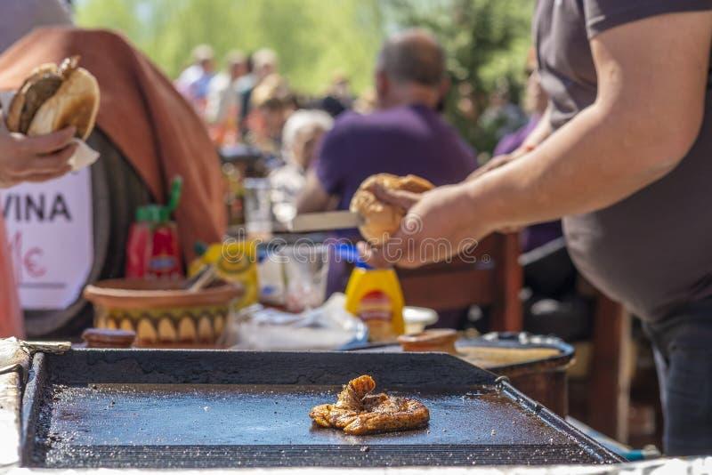 De kerel maakt hamburgers met gebraden rundvlees royalty-vrije stock afbeelding