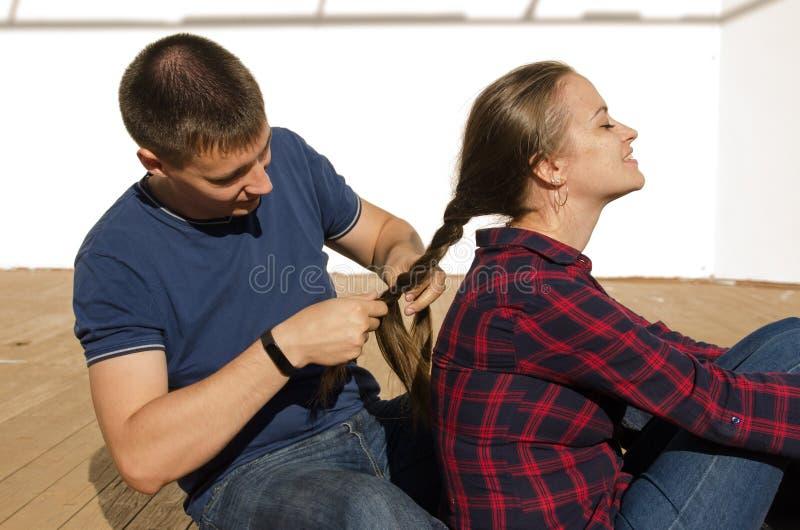 De kerel met een kort kapsel vlecht een meisje met lang donker haar en een plaidoverhemd stock foto