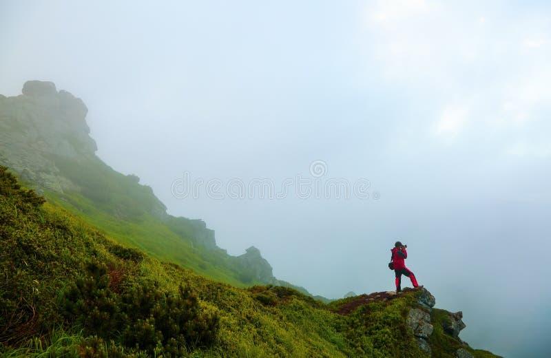 De kerel met fotocamera blijft op de steile rots in de mist stock afbeelding