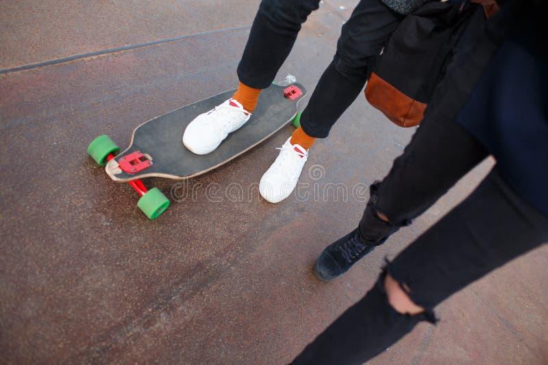 De kerel met het meisje op de pijler het meisje berijdt op het skateboard royalty-vrije stock foto