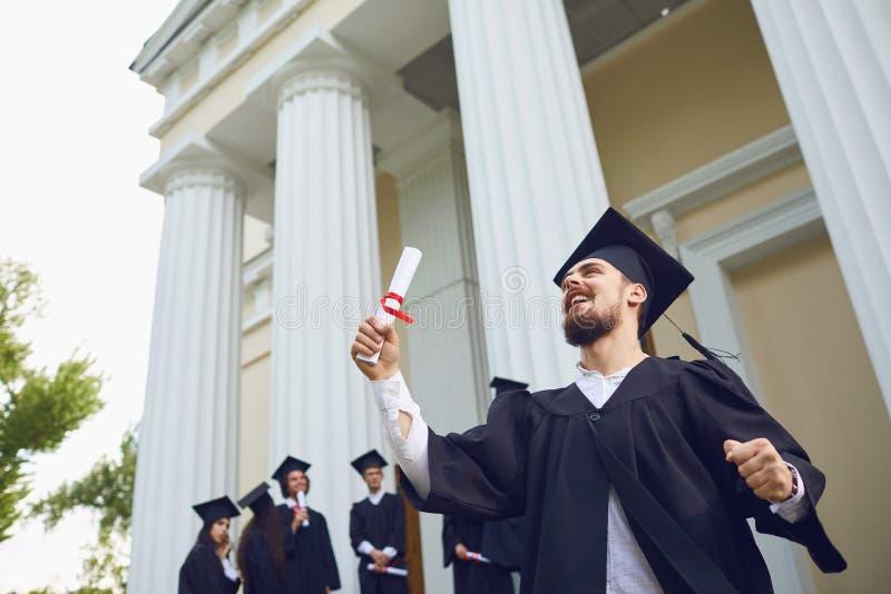 De kerel met de rol glimlacht tegen de achtergrond van mensen met universitaire diploma's stock foto