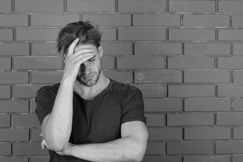 De kerel met varkenshaar in donkerblauwe t-shirt lijdt aan hoofdpijn stock afbeelding