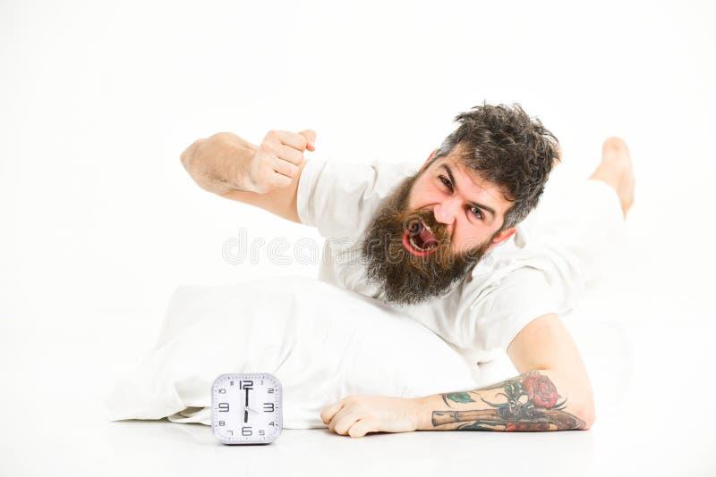 De kerel met woedend gezicht slaat wekker stock foto's
