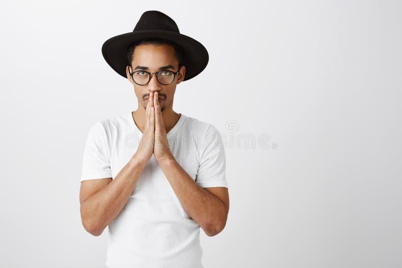 De kerel moet oplossing kalmeren en vinden Het zenuwachtige knappe mannelijke model in modieuze zwarte hoed en eyewear, het houde royalty-vrije stock afbeelding