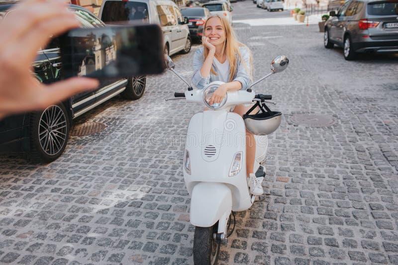 De kerel neemt beeld van meisje in helmzitting op motorfiets Zij leunt aan het en glimlacht op camera Het meisje is royalty-vrije stock afbeelding