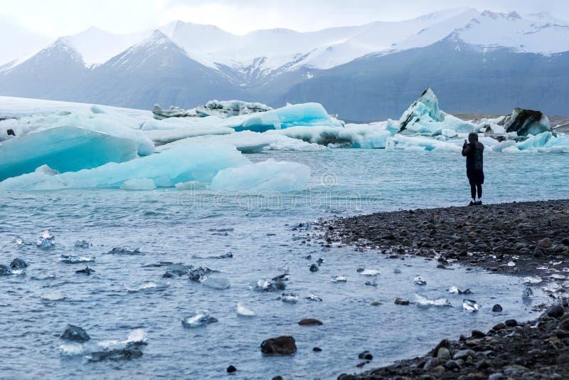 De kerel neemt beelden van de ijsberg en de gehele gletsjer in IJsland royalty-vrije stock fotografie