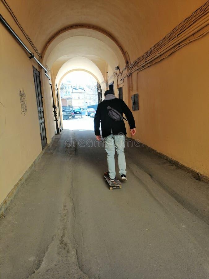 De kerel op de skateboardbladeren op de straat stock foto