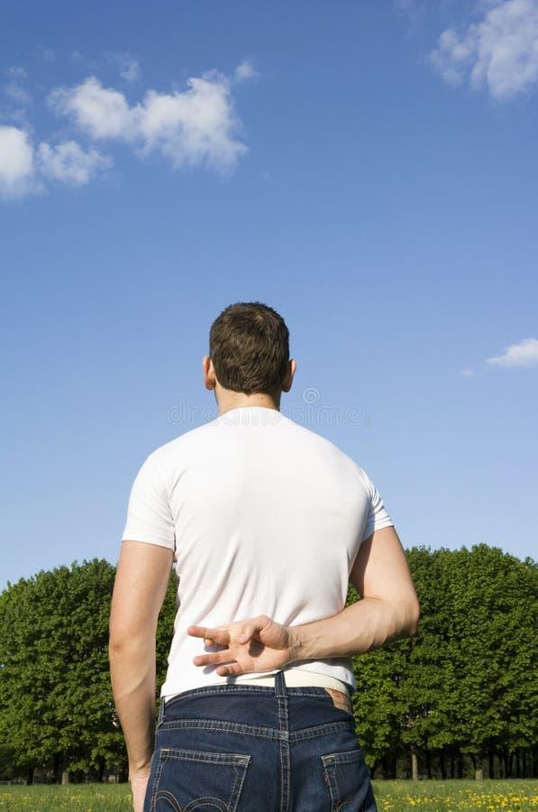 De kerel in parkvingers wordt gekruist achter een rug stock foto's