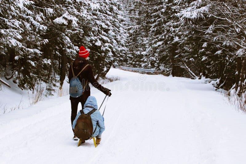 De kerel rolt een meisje op een slee langs een snow-covered weg door de donkere bosa-groep mensen die van het snowshoeing op a ge royalty-vrije stock foto's