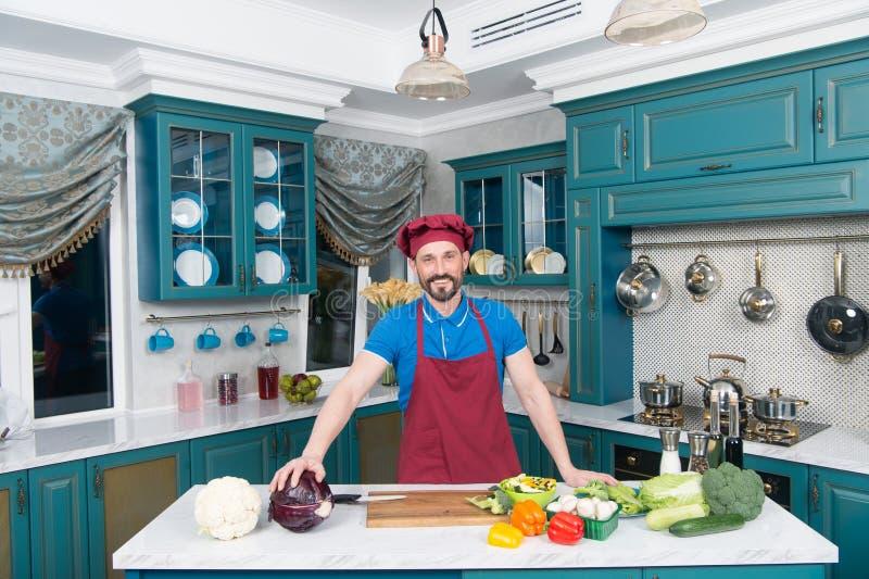 De kerel in schort en de hoed in de keuken maakten salade voor veganisten met sla en courgette Het knappe concept van de mensen t royalty-vrije stock afbeeldingen