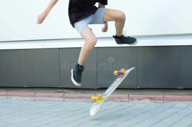De kerel springt omhoog op een skateboard Gesmeerde motie stock foto's