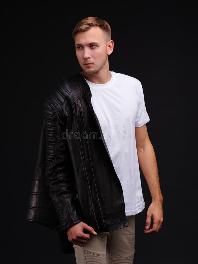 De kerel in T-shirt en een jasje op één hand, kijken weg met een ernstige blik en houden van hem zak indienen stock foto