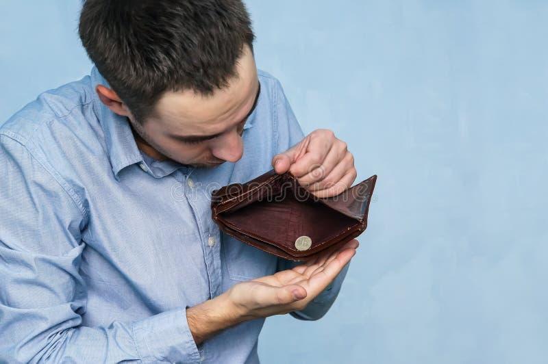 De kerel trekt de laatste roebel uit een lege beurs terug royalty-vrije stock foto's