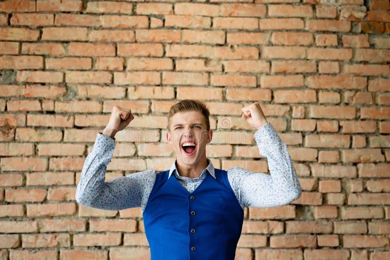 De kerel verheugt zich in de overwinning Bakstenen muur Omhoog opgeheven handen royalty-vrije stock foto
