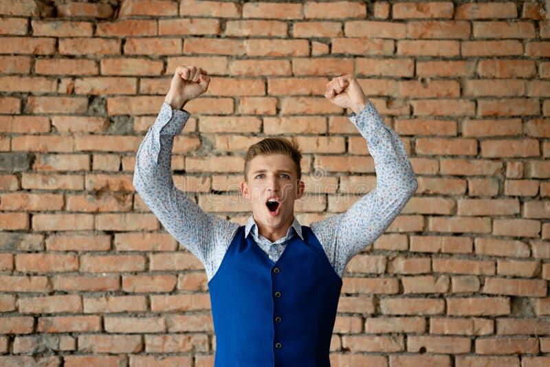 De kerel verheugt zich overwinning dichtbij de bakstenen muur Zaken stock foto