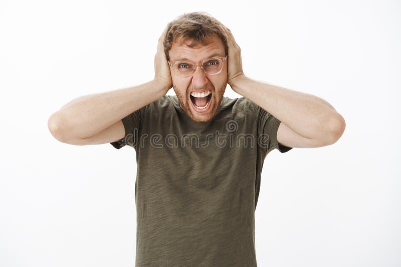 De kerel verliest bui die met hevig lawaai bij nacht schreeuwen zijn uit luid met boze verontwaardigingsuitdrukking die oren beha stock foto's